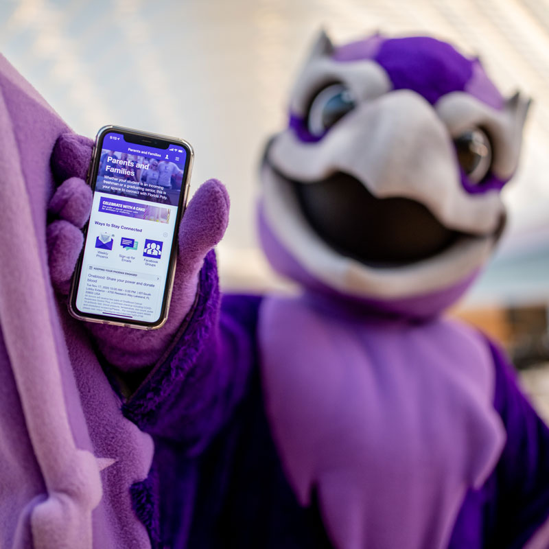 image of mascot holding phone with mobile app on screen