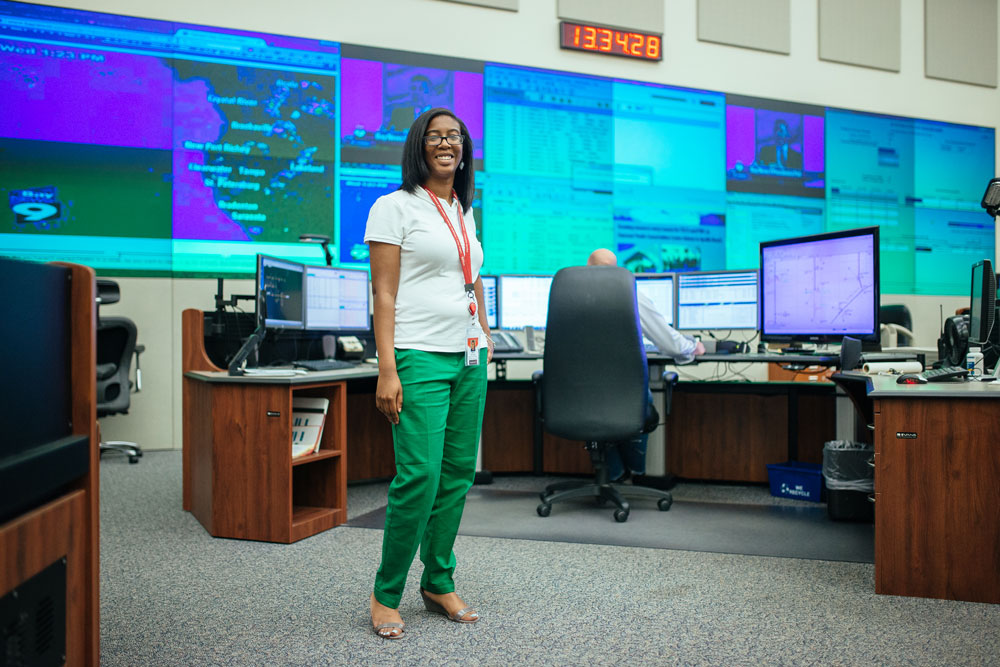 Female student in green pants stands in front of screens and clock
