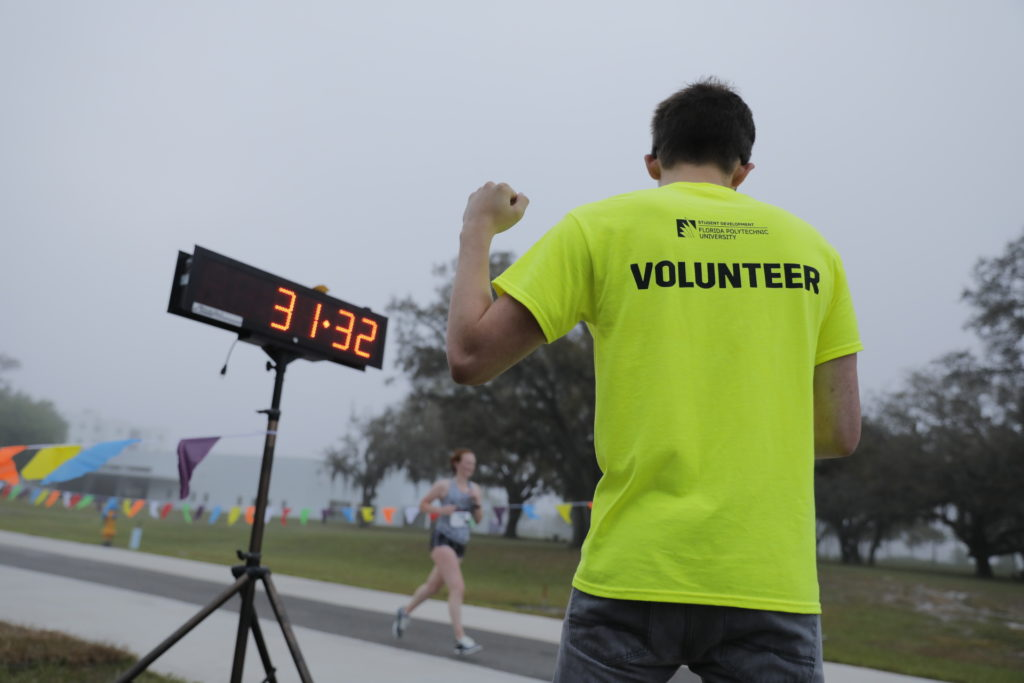 Florida Poly student volunteer checking the time at the end of the 2019 Pi Run.