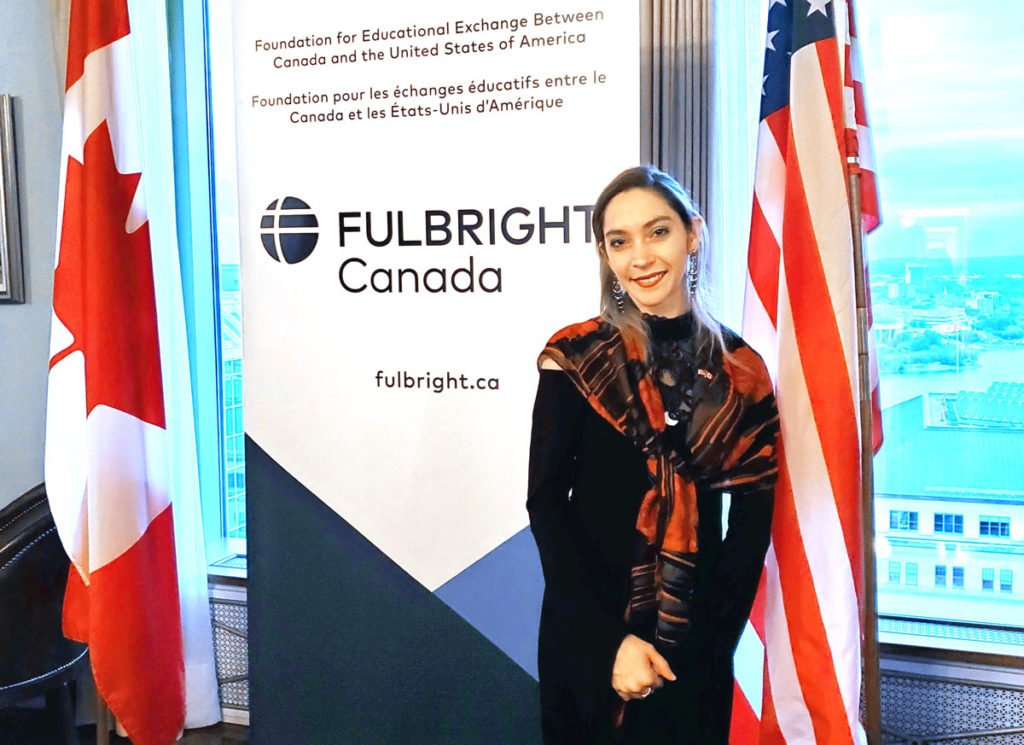 Light skinned female standing in front of pull up banner and Canadian and American flags.