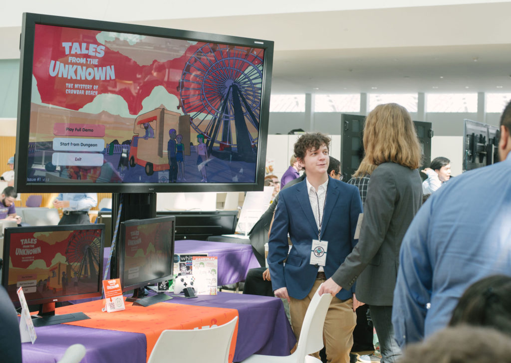 Male student in front of monitor screen explaining his game.