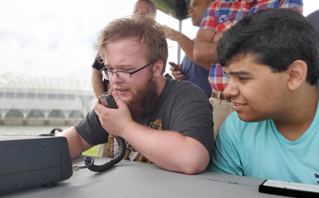 Two pale skinned males sitting at desk outside with ham radio controller.