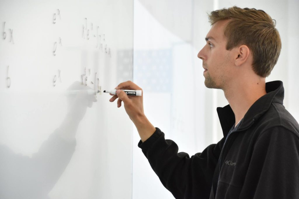 Florida Poly male student solving integral bee equation on whiteboard.