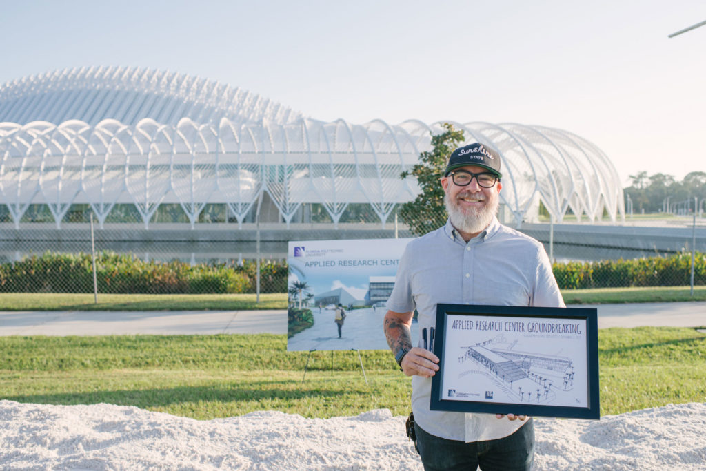 Light skinned male holding up a framed sketch of the Applied Research Center building.