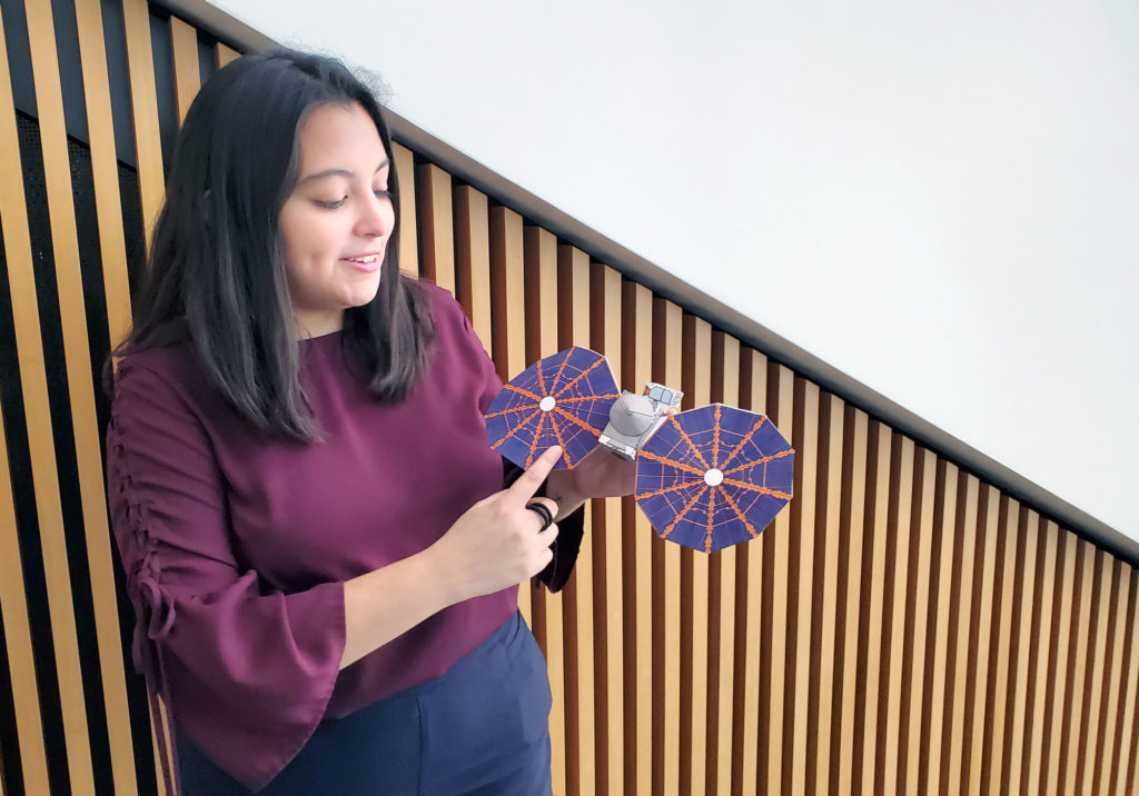 Mechanical engineering major Elise Araiza shows a model of Lucy, a planned NASA space probe that will travel to Jupiter's Trojan asteroids to collect data and images.