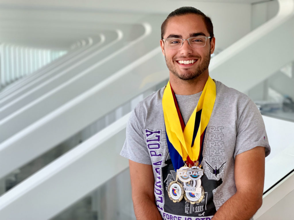 Male Florida Poly student standing inside with medals.