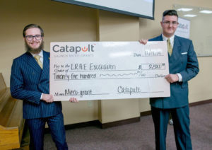 Two light skinned males holding up giant check