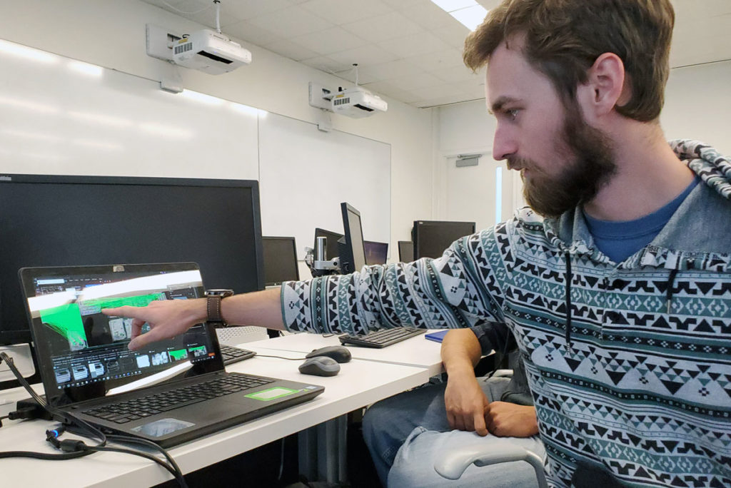 Light skinned male pointing at computer screen.