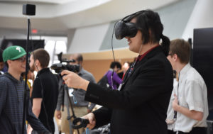 Florida Poly student holding up VR controllers at Game EXPO