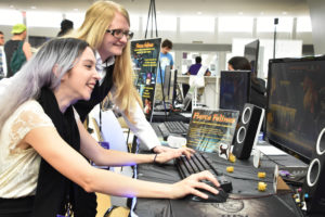Two female Florida Poly student playing video game during the Game Expo