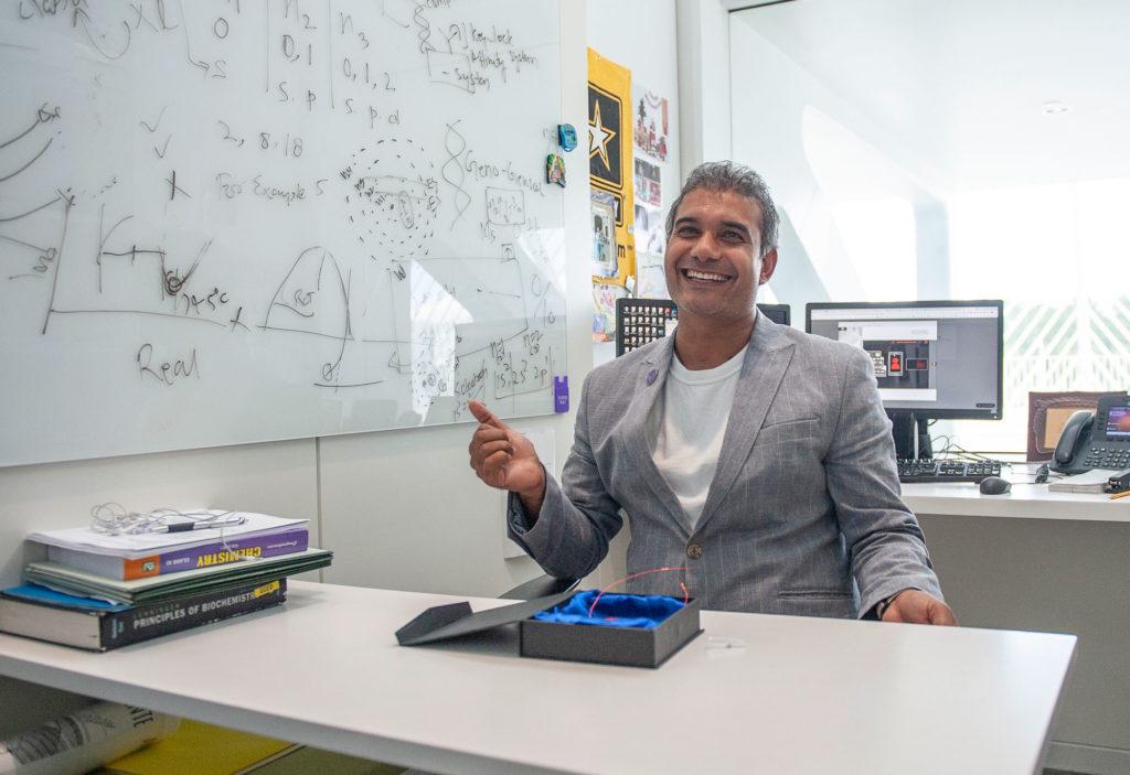 Medium skinned male smiling in office.