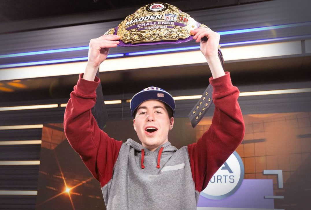 Florida Poly male student holding up EA Madden Champion belt.