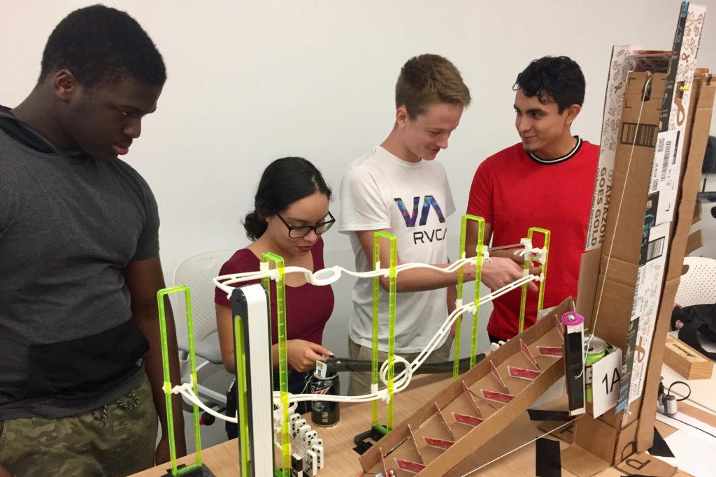 Four Florida Poly students test their Rube Goldberg machine