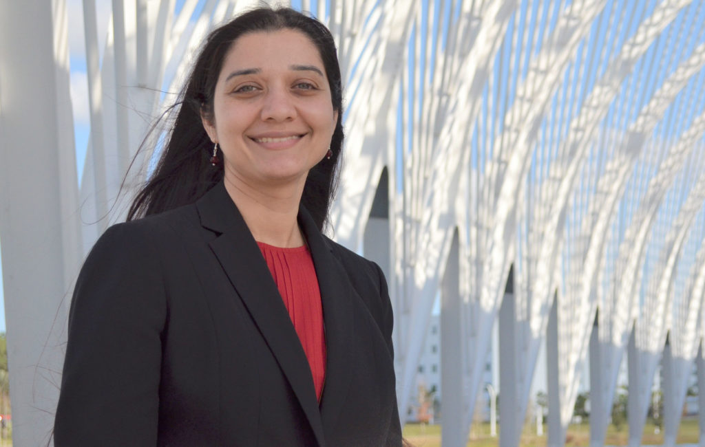 Female professor standing outside of Innovation, Science, and Technology (IST) Building at Florida Polytechnic University.