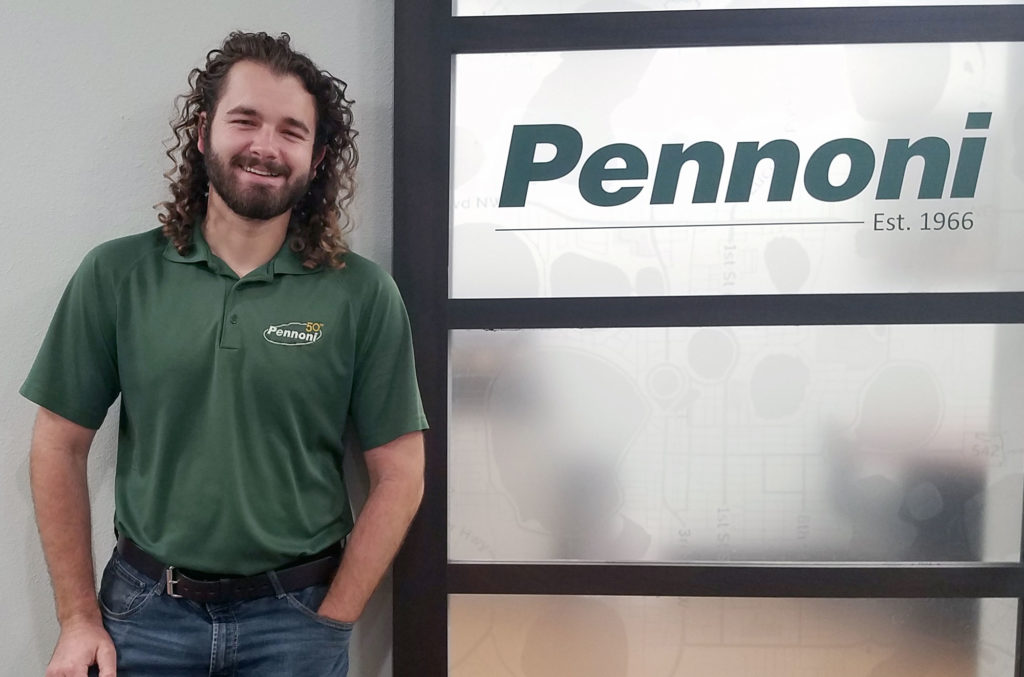 Light skinned male with long hair in front of Pennoni sign.