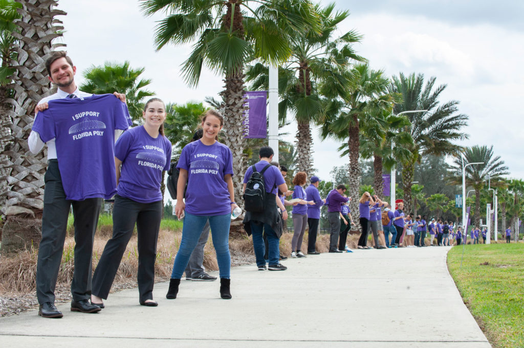 Group of students holding and wearing purple tshirts in a line outside.