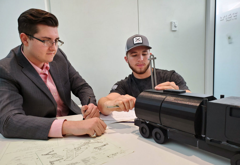 Two male student working on a research project.