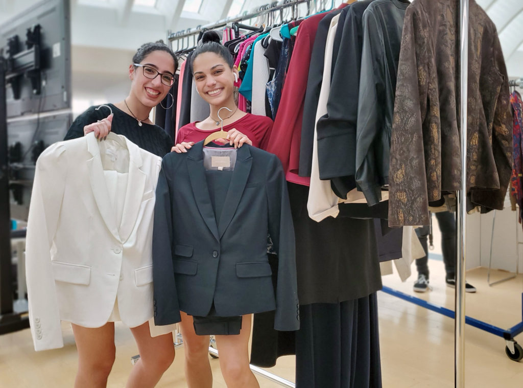 Two light skinned females holding up suits on hangers.