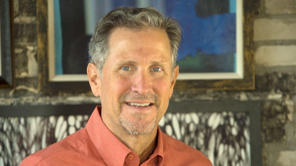 Light skinned male smiling in orange shirt.