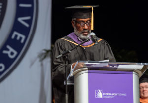 Dark skinned male wearing a graduation cap and gown presenting.