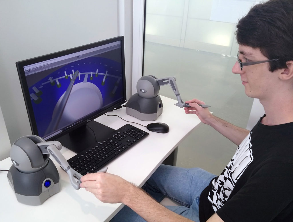 Light skinned male sitting in front of a computer.