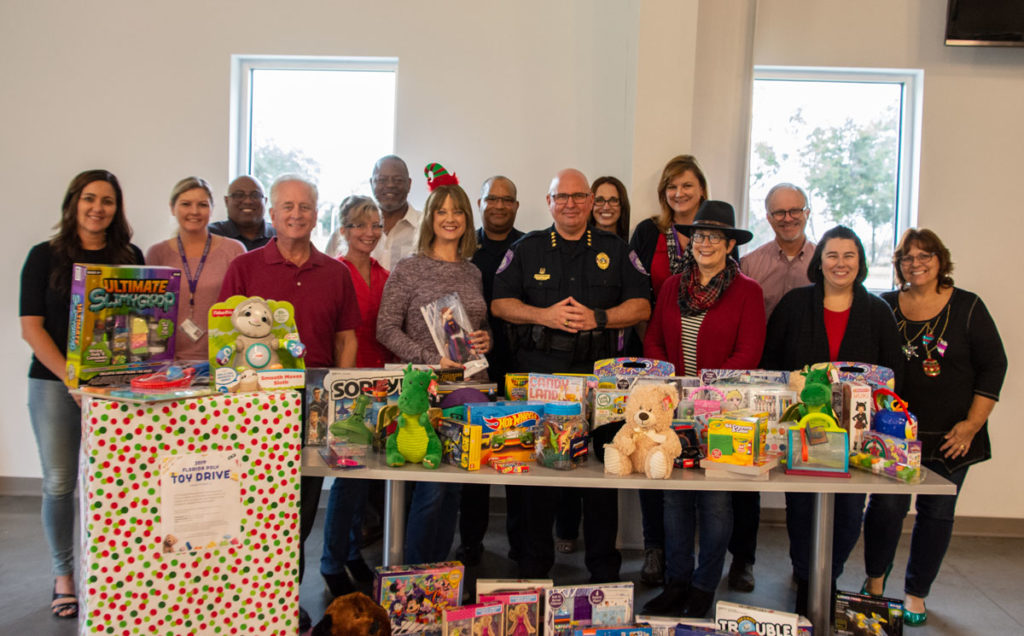 Group of Florida Poly employees in front of table with toys.